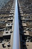 The long line of the railroad track. Looking down on the long line of the rusty railroad tie on the track of the rail road in the summer sun royalty free stock photos