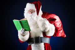 Long list. Traditional Santa Claus reading a list of good boys and girls in his notebook. Christmas Stock Photography