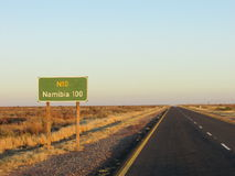 Early morning shot of Long lonely Road to namibia just before full sunrise. Long straight road to namibia showing lonely strech through the kalahari desert Royalty Free Stock Images
