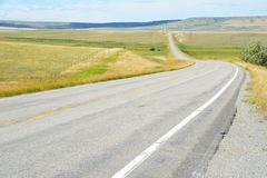 A long, lonely road in Whoming travels for miles. Miles of road stretches straight in Wyoming Royalty Free Stock Image