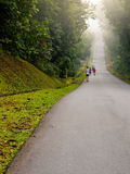 Long Long Road. Runners running along a hilly road in the early morning Stock Images