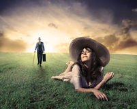 Long for love. Beautiful woman lying on a green meadow with gentleman approaching on the background Stock Photos
