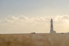 Long, low angle shot of lighthouse beyond bokeh effect sand stock photo