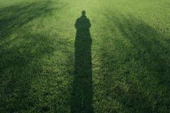 Long man shadow on grass. Man shadow low sunlight on grass background sunny shadows green Royalty Free Stock Photos