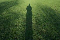 Long man shadow on grass Royalty Free Stock Photos
