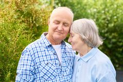 Long Marriage with Love. Waist up  portrait of loving senior couple embracing tenderly posing for camera in beautiful garden Royalty Free Stock Photo