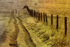 The long meadow road. An abstract textured background of a road with a fence in the country Stock Photography
