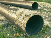 Long metal industrial pipes on ground. Repairing of water system. Long metal industrial pipes laying on ground. Repairing of the water delivery system. Open royalty free stock photography
