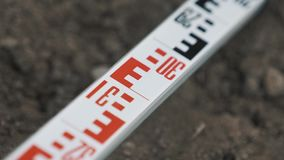 Long metal metric ruler with red and black marks laying in ditch over dirt stock video
