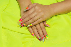 Long nails. Two female hands on a bright fabric, neat manicure with creative nails different colors. fluorescent art. Bright lemon background. Studio shot Stock Photography