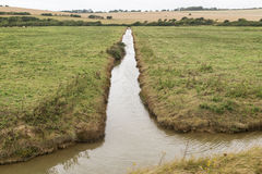 Long and narrow irrigation canal built to carry water in farm. Long and narrow irrigation canal built to carry water used for farming, surrounded by green fields stock photography