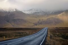 Long narrow road with beautiful hills and mountains covered in fog royalty free stock photos