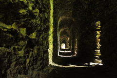 Long narrow tunnel in medieval castle. Inside a secret passageway of a castle ruin. Sunlight shines through the shafts Royalty Free Stock Photos
