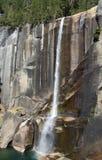 Long narrow waterfall; Yosemite Valley. Narrow waterfall cascading over granite cliffs with a small rainbow visible at Yosemite Vally, in Yosemite National Park stock image