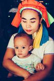 Long Neck Woman is sitting with her child. Tribal village Northern Thailand. Long Neck Woman wearing at traditional costume is sitting with her child. Tribal royalty free stock image