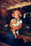 Long Neck Woman is sitting with her child. Tribal village Northern Thailand. Long Neck Woman wearing at traditional costume is sitting with her child. Tribal stock photos