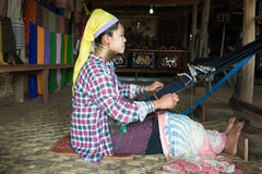 Long-necked Kayan Lahwi woman weave on traditional device Royalty Free Stock Photos