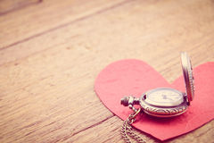 Long necklace antique style pocket watch with a red paper heart. Royalty Free Stock Photos