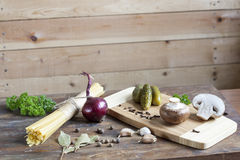 Long Noodles Linguine, pickled cucumbers gherkins, Champignon mushrooms, herbs, spices and vegetables on wooden table Stock Photo