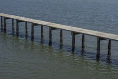 Long old concrete bridge over the sea. With some shellfish in pile royalty free stock photography
