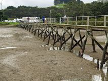 Mudflat pier. Long, old jetty built over mudflats  to reach the channel where the ferry docks Royalty Free Stock Image