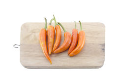 Long orange chili with chopping block. Long orange chili on brown chopping block Stock Photo