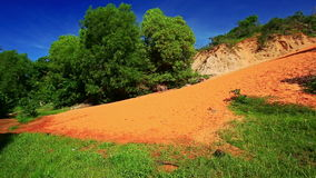 Long Orange Sand Hill Slope among Trees Green Grass. Camera shows long orange sand hill slope among beautiful green trees and bright green grass against deep stock footage