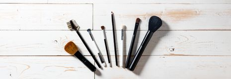 Long panorama for display of professional makeup brushes over wood. Long panorama for display of professional makeup accessories with blush and eyeshadow brushes Stock Image