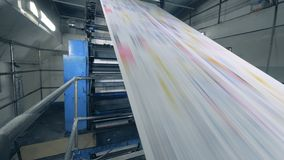 Long paper sheets moving on a line at a print office, factory equipment in work. stock video footage