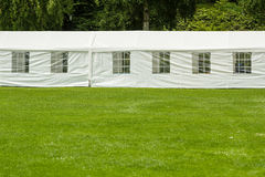 Long party tent. Long white party tent at the end of big lawn in park Stock Images