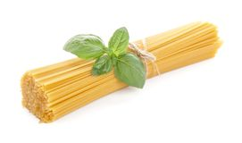 Long pasta raw isolated with basil leaf on white background Stock Photo