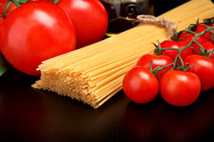 Long pasta raw isolated on black with tomatoes and olive oil. Long group of raw pasta tied with string isolated on black board with tomatoes and carafe full of Royalty Free Stock Image