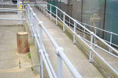 Long pathway with sliver railings leading to a corner Stock Photos