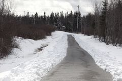 Long paved trail in snow Royalty Free Stock Photos
