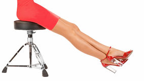 Long perfect female legs. Wearing high heels red shoes sitting on metal stool isolated on white background Royalty Free Stock Image
