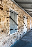 Long perspective view of a stone building with stable like doors. And shutters Stock Photography