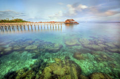 Long pier dan beautiful coral at Mabul Island Royalty Free Stock Photo