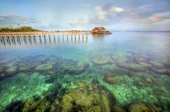 Long pier dan beautiful coral at Mabul Island.  Royalty Free Stock Photo