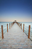 Long pier heading to the sea under the beautiful blue sky. Stock Photography