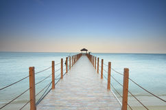 Long pier heading to the sea under the beautiful blue sky. Stock Photos