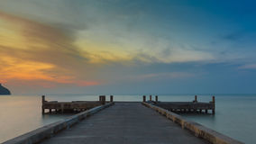 Long pier leading into the seacoast before sunrise Stock Photography