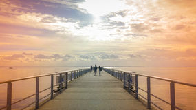 Long pier over the sea shore, evening autumn light leak, sihouette of walkers Stock Images