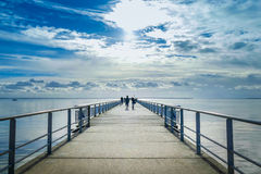 Long pier with sihouette of walkers Royalty Free Stock Photo