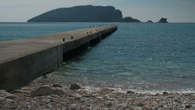 A long pier stretches to the sea with mountains in sunny weather. stock video footage