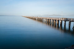 Long pier stretching out in the water. With land in the horizon Royalty Free Stock Image
