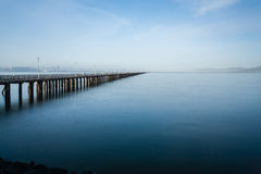 Long pier stretching out in the water. With land in the horizon Stock Photo