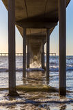 Long Pier in the Surf. A sharp capture of the surf crashing against the supports of this pier.  The falling sun lights the interior of this lengthy span to its Royalty Free Stock Photography