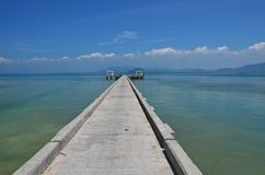 Long piergiong into ocean. Long concrete pier giong deep into the ocean on ko mook island, thailand Royalty Free Stock Images
