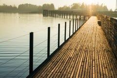 Long pilier en bois de promenade au-dessus de l'eau dans la lumière égalisante d'or avec une silhouette de marche de paysage et d image stock
