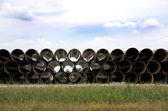 Long Pipe Stacked Next To Highway. Long large pipe stacked beside highway for construction Stock Images